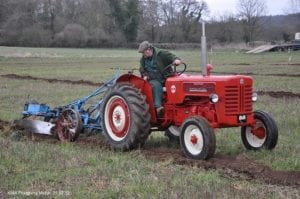 Photo of man working the ground on red tractor
