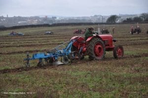 Photo of man working the ground on a red tractor.