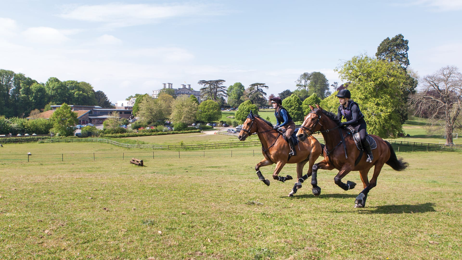 Two Equine students riding across field, with the Main House in the background
