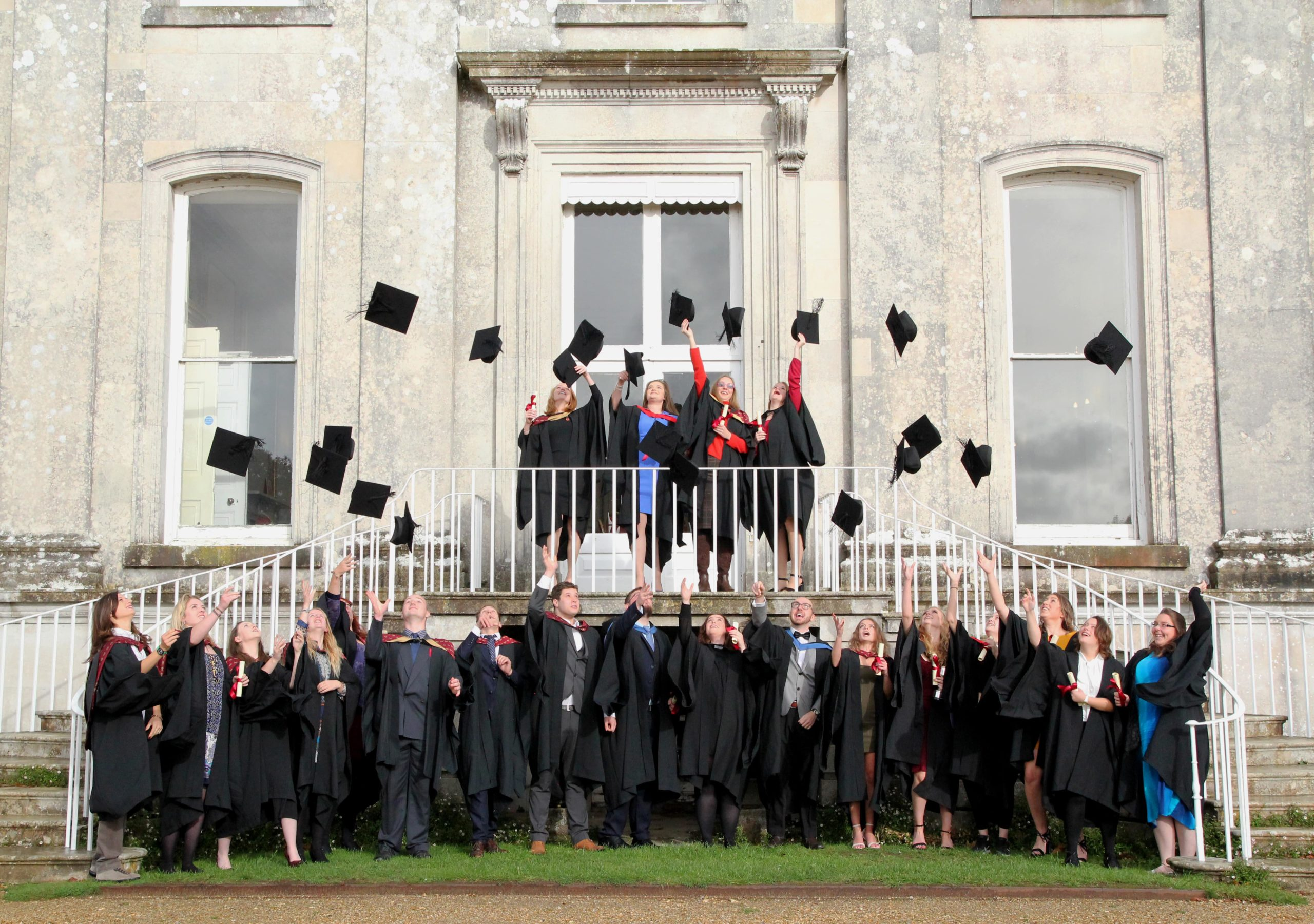 Group of students in graduation gowns throwing their graduation caps stood on the steps of the back of the Main House at Kingston Maurward
