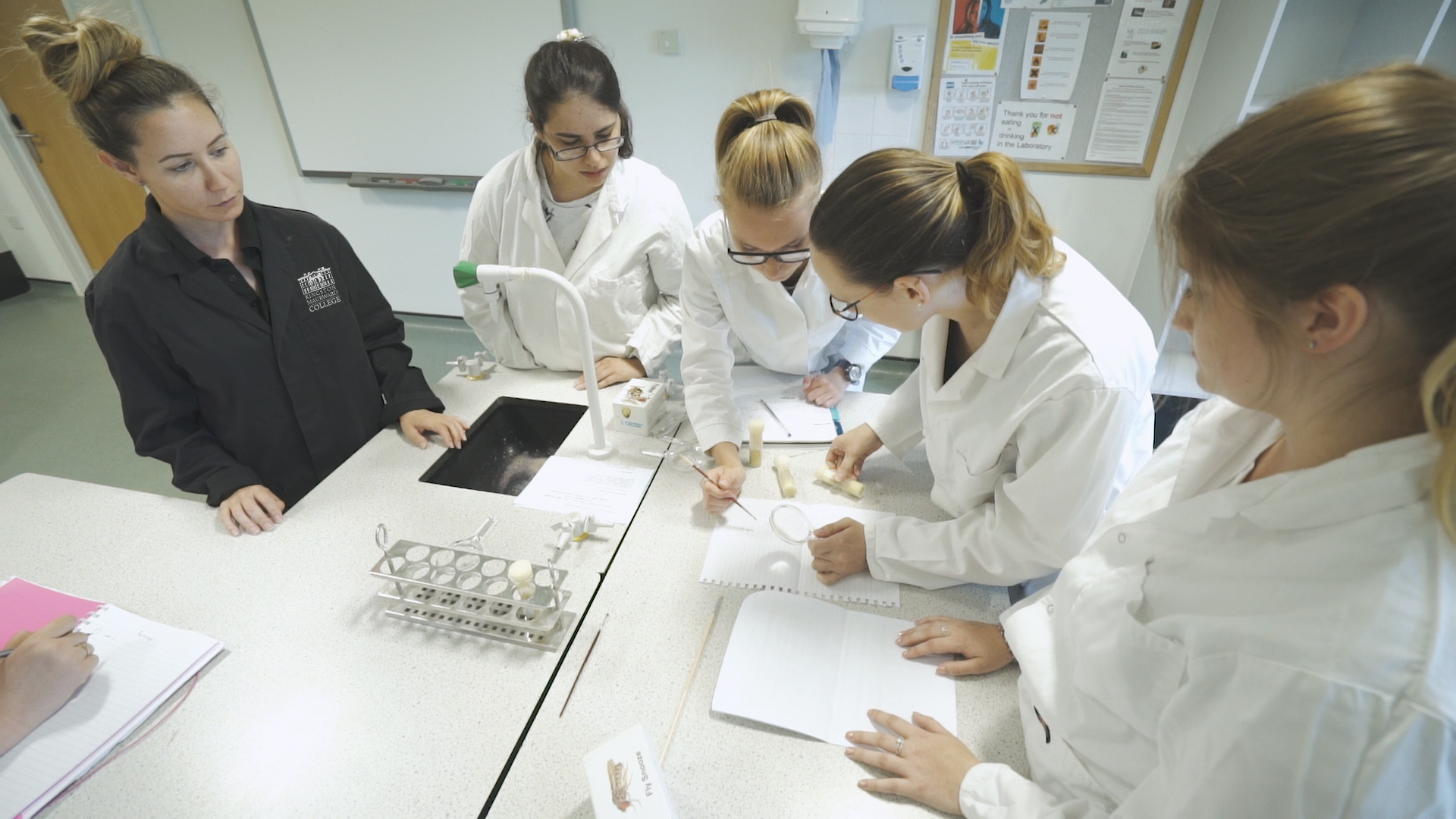 Group of students in lab coats studying, stood over a desk.