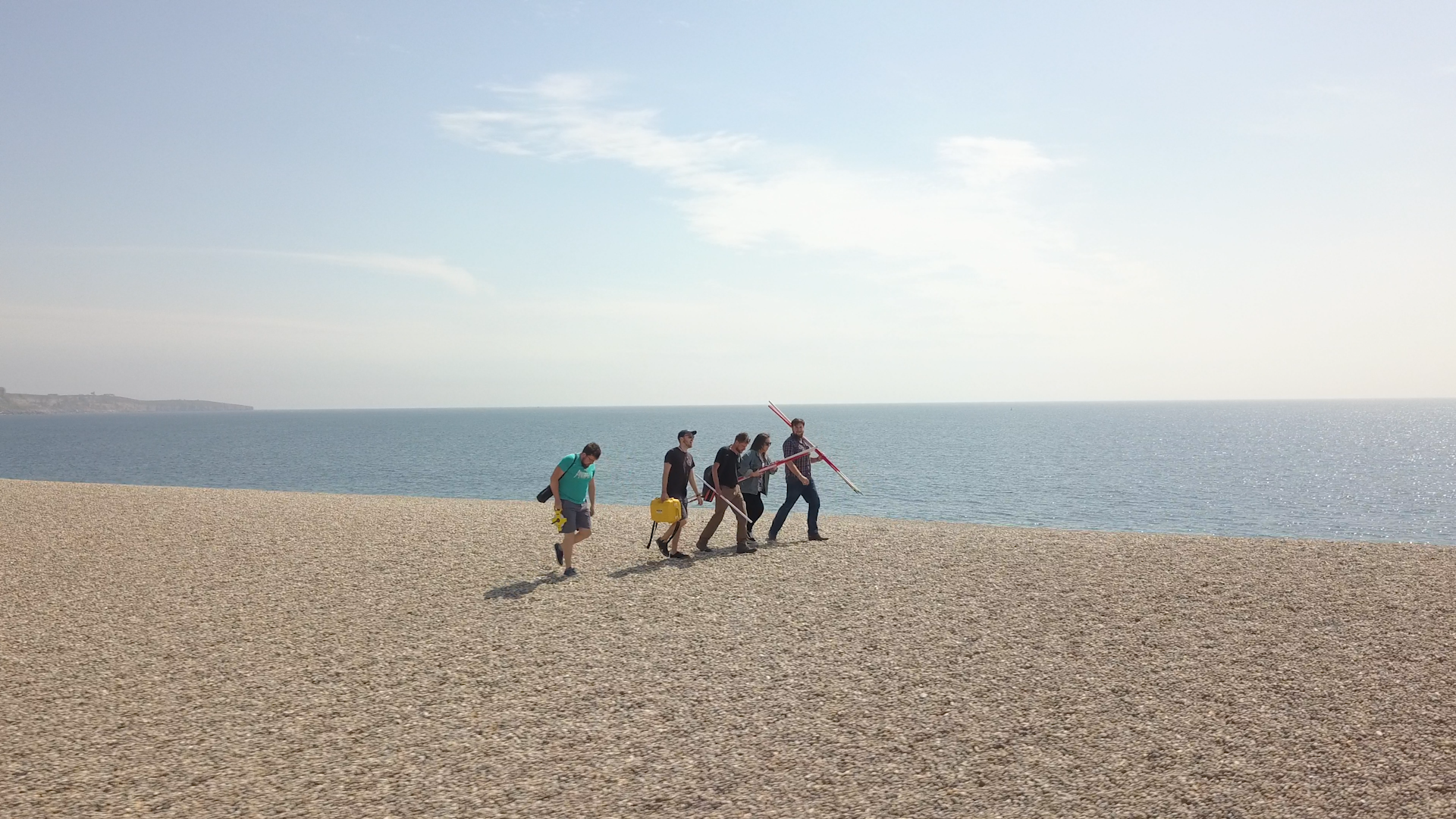 Group of students walking on Chesil Beach carrying equipment relating to Marine Ecology and Conservation
