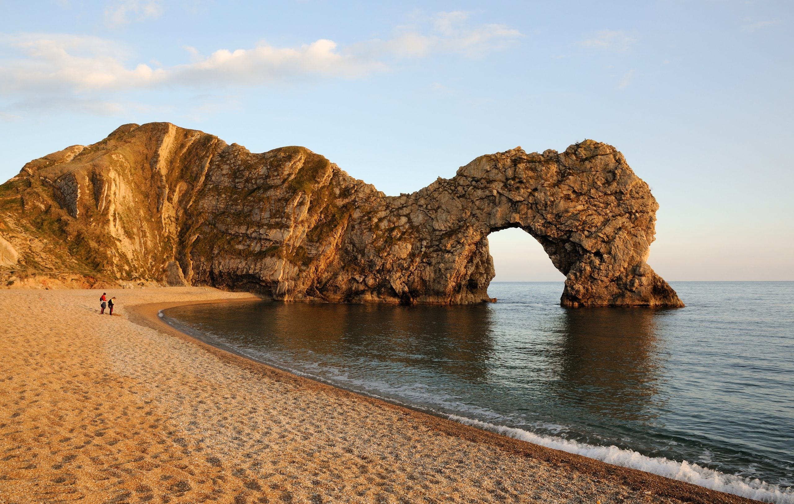 Landscape photo of Durdle Door with the sun shining down on the beach