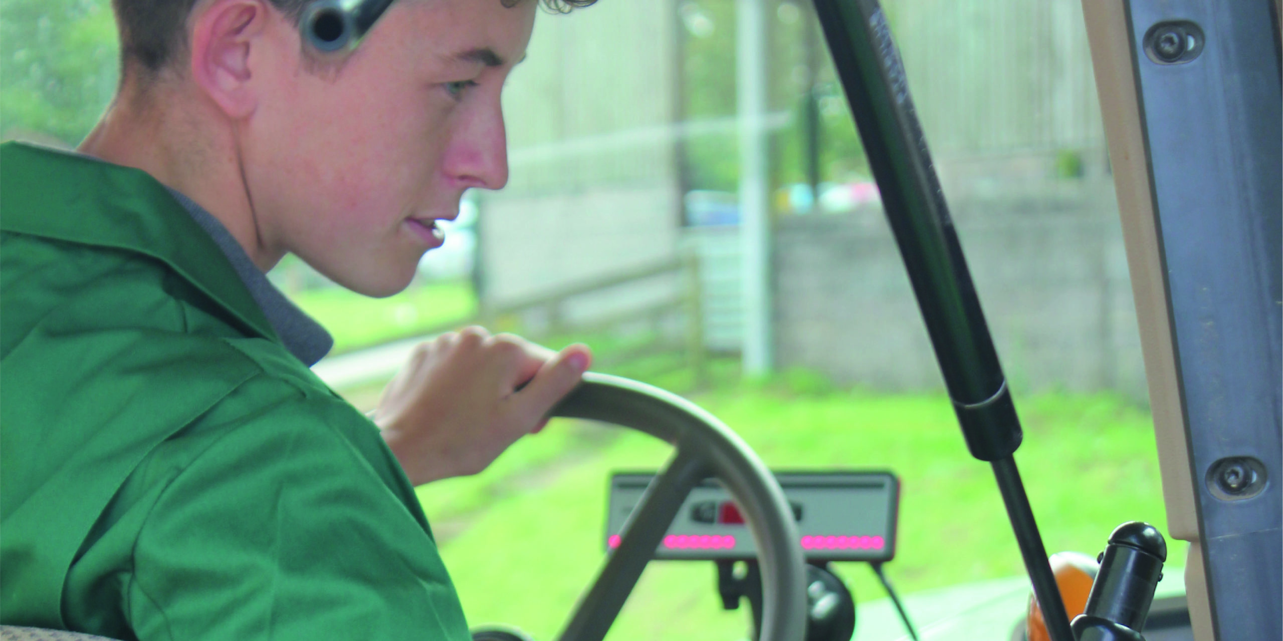 Close-up of student driving tractor. Student is looking right, down towards controls.
