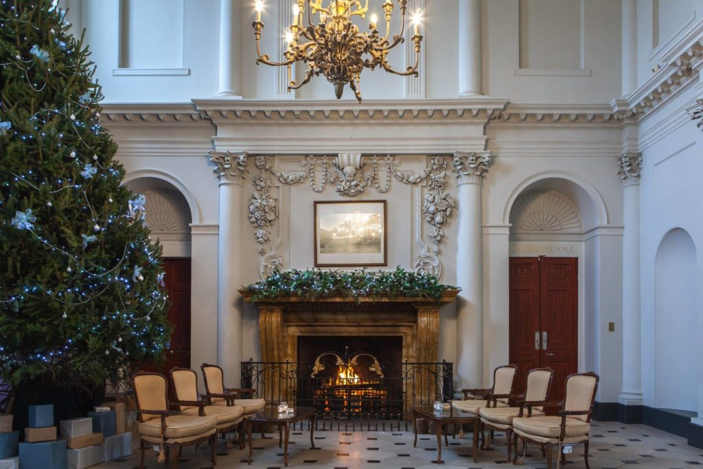The Grand Entrance Hall with Christmas tree and lit fireplace which has foliage along the mantle piece