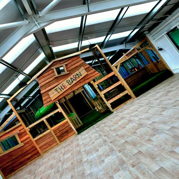 Front of the soft play area in The Barn with wooden front and play equipment visible in the background