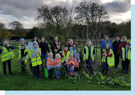 Line up of children in high vis and staff behind holding branches, education and group visits