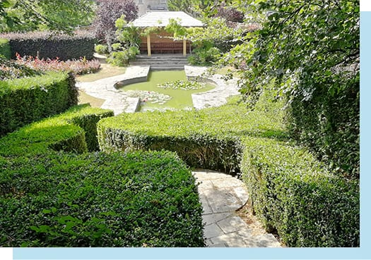 Curved hedges and pathway leading down to The Red Garden which features a pond and brick shelter