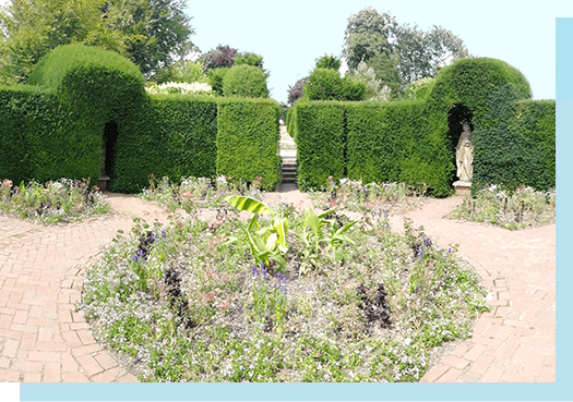 The Brick Garden, featuring a central flower bed and statues embedded in green hedges with a brick pathway around flower bed