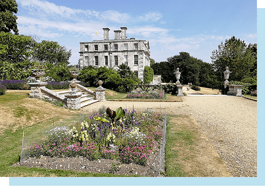 Side of Main House photographed from the terrace to include beds, decorative stone work and stone staircase