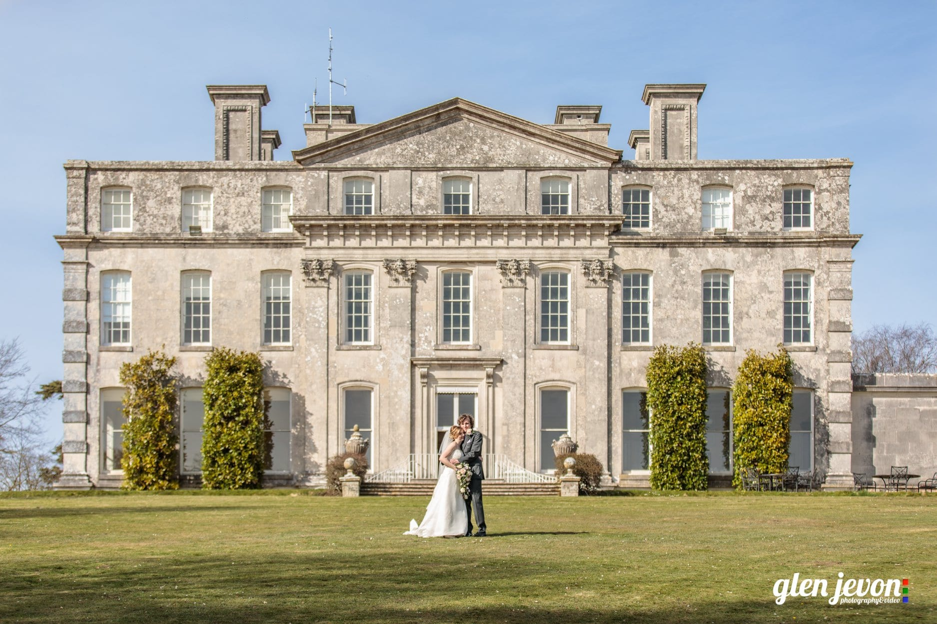 Bride and groom stood on the lawn with the Main House in the background on a sunny day