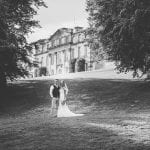 Bride and groom stood on the lawn with the side of the Main House in the background. Black and white photograph. Atlas Photography