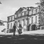 Bride and groom walking back towards the Main House across the lawn, black and white image. Atlas Photography