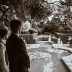 Groom stood in The Red Garden, pond in the background, guests stood waiting for Bride to come down.