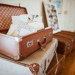 Suitcases stacked with the top open with letters and notes filled and coming out