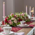 Table scape with flowers in the centre, tea cups and napkins and pink candles in holders