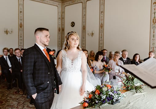 Bride and groom getting married in The Pengelly Room with people sat in the background.