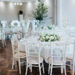 Maurward Hall with circular tables, white chairs and table cloths, white centre flowers with large LOVE letters in the background, gold candle holders and white candles