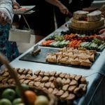 Catering image including a platter of cheese, quiches and vegetables