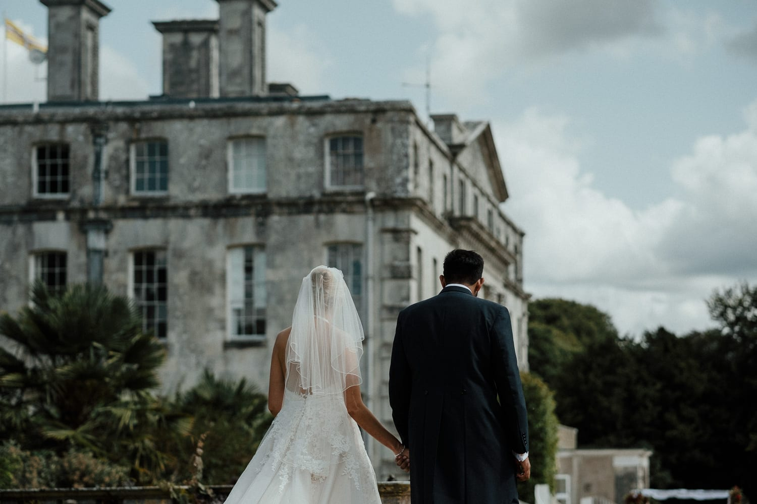 Bride and groom hand in hand walking towards the Main House along the terrace