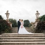 Bride and groom on terrace stone steps with foliage and brickwork on either side