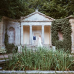 Bride and Groom stood by Grecian Temple - Atlas Photography