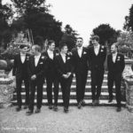 Groom party walking down stone steps in black and white photo