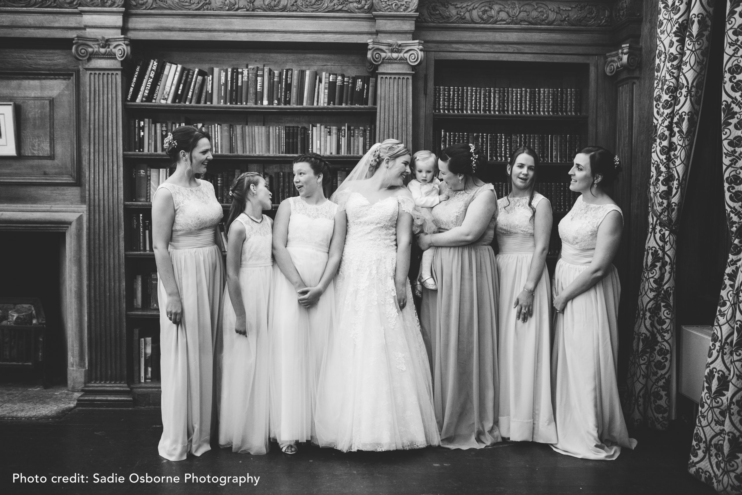 Bridal party lined up in front of bookshelves in the Old Library