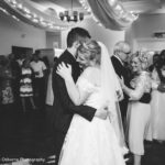 Bride and groom embraced dancing in Maurward Hall surrounded by guests