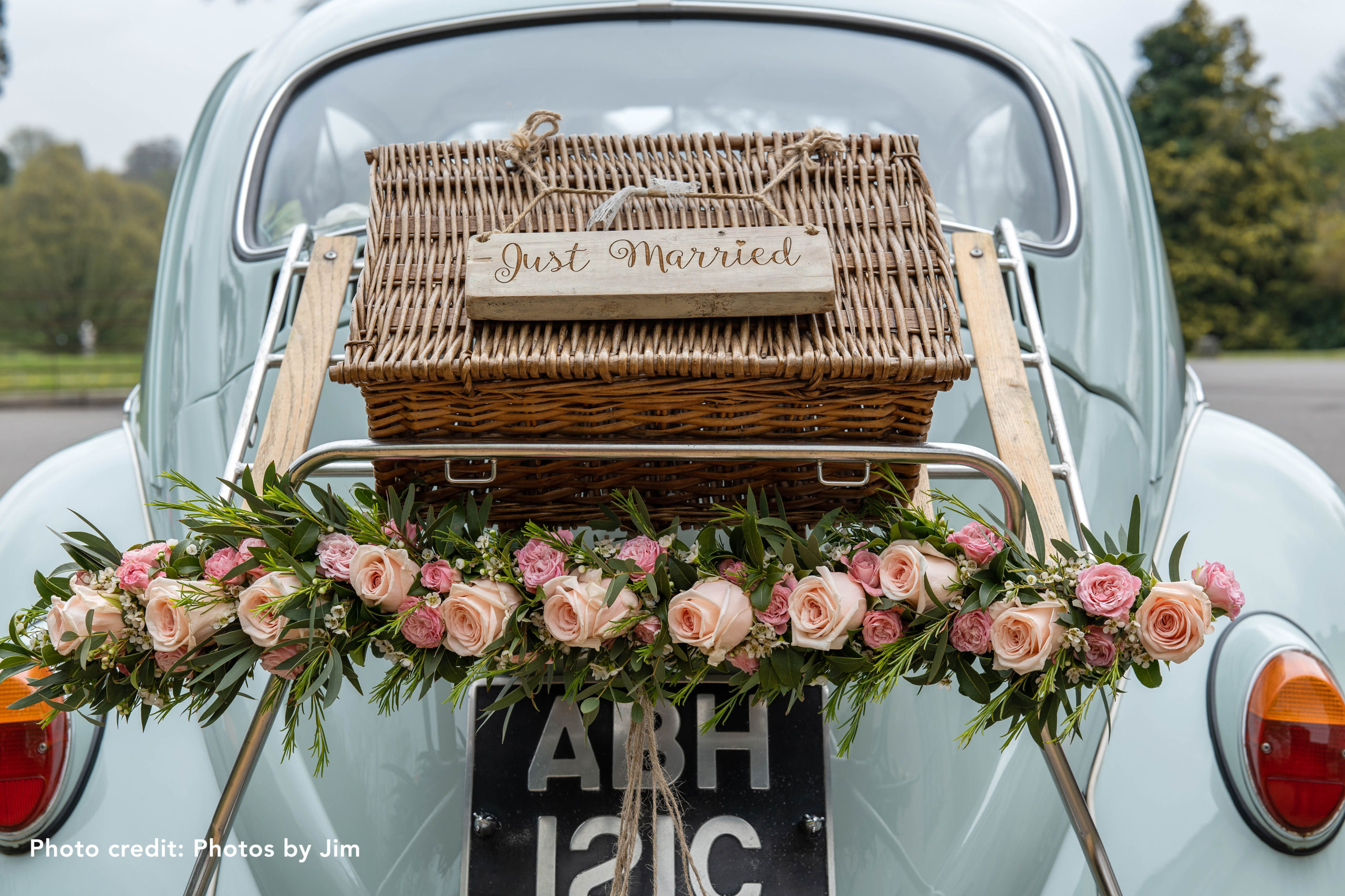 Light blue car with Just Married on a picnic basket on the back, wreath of flowers including light pink roses.