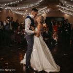 Bride and Groom in Maurward Hall, dancing together with friends and family surrounding them