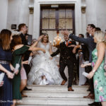 Bride and groom walking down entrance steps, people either side throwing confetti