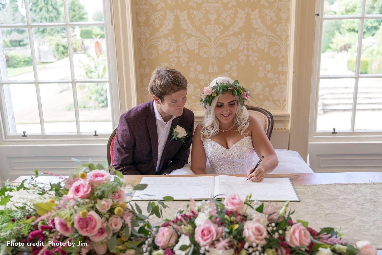 Couple signing register in Whatmoor Room